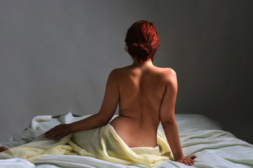 Back view of a naked woman sitting in bed covered with sheets