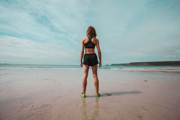 Young athletic woman standing on the beach