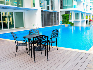 Black table and chairs near a cool pool