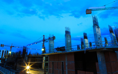 Construction site with cranes on twilight sky