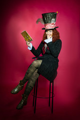 Young woman in the similitude of the Hatter reading book sitting