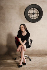 Young attractive business woman sitting on office chair