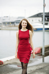 Woman at red dress walk on wharf
