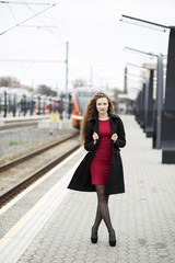Woman at red dress and black overcoat