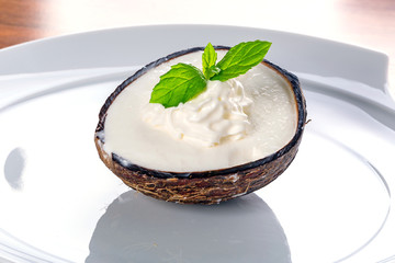 Coconut ice cream in coco shell on the plate