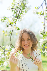 beautiful young brunette woman standing near the apple tree on a