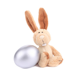 White toy rabbit with silver egg.