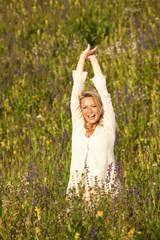 Glückliche Frau mit ausgestreckten Armen in einer Blumenwiese