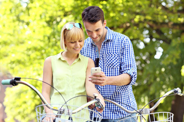 Young couple on bikes checking the cellphone