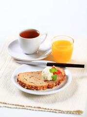 Bread with cheese spread, cup of tea and orange juice