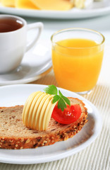 Bread with butter, cup of tea and orange juice