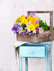 Beautiful flowers in crate on wooden stand on light background