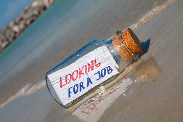 """Bottle with a message """"Looking for a job"""". Unemployment concept."""