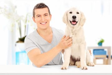 Man posing with his dog seated at table indoors