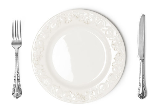 Vintage plate, knife and fork on white background