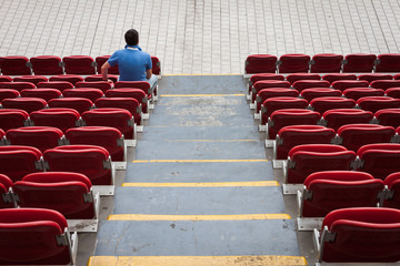 Empty stadium seats with a man alone