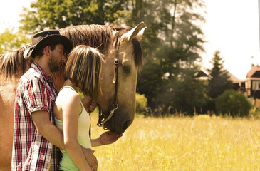 Young beautiful couple sitting in the grass with a horse