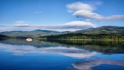 Boat on morning lake with clouds and reflection