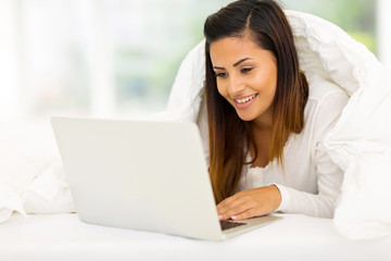 woman using laptop computer while lying on her bed