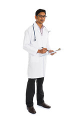 indian male doctor full body writing on board isolated on white