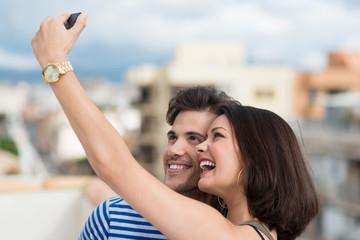 glückliches paar fotografiert sich mit dem handy