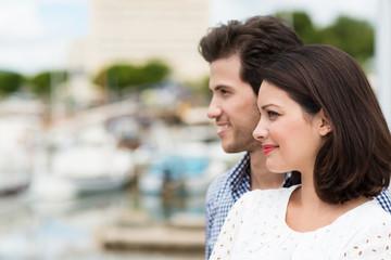 lächelndes paar schaut auf den hafen