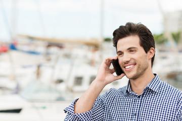 mann am hafen telefoniert mit smartphone