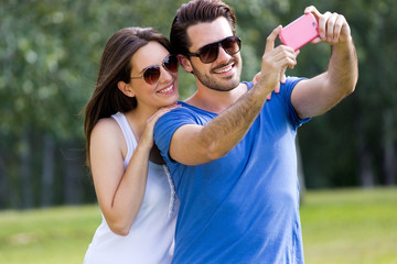 Happy young couple taking selfies with her smartphone in the par