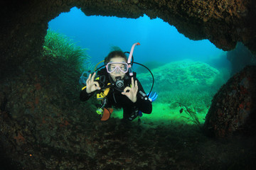 Young woman scuba diving in underwater cave