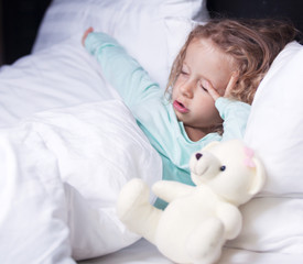 little girl stretches in bed with a toy bear