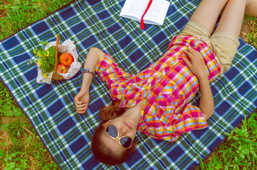 Background girl lying on plaid with glasses next book and a bask