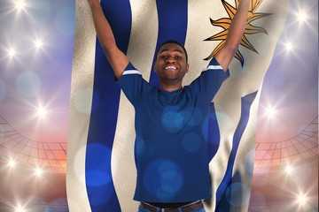 Composite image of cheering football fan in blue jersey holding