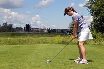 Female golfer prepares to tee off