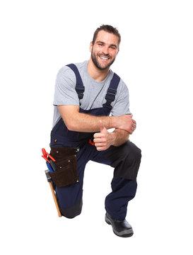 Portrait of smiling worker kneeling with hand doing ok gesture