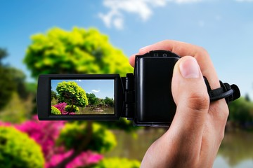 Video camera or camcorder recording flora in japanese garden