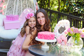 Young beautiful women and her daughter celebrate birthday with a