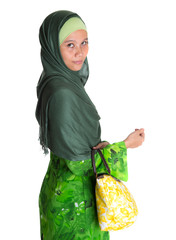 Muslim woman in green dress, hijab with yellow handbag