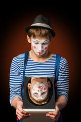Clown grimacing before a mirror