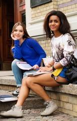 Multi ethnic girls students near university building entrance