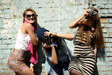 urban girls have fun with vintage photo cameras outdoor near gru