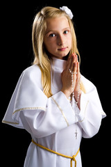Cute blonde girl in first communion alb on black background
