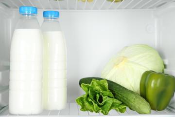 Milk bottles, vegetables and fruits in open refrigerator.