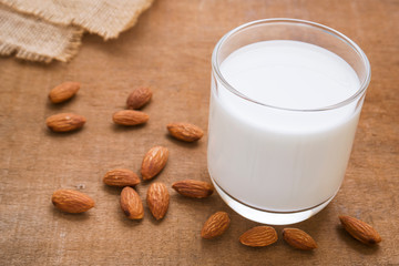 Almond milk and almond on wooden table