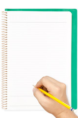 Hand holding the pencil on blank page of green cover notebook