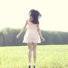 Girl in a dress jumping in a field