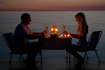 A young couple share a romantic dinner with candles on the beach