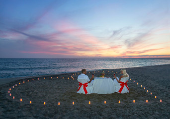 Lovers couple have a romantic dinner with heart of candles