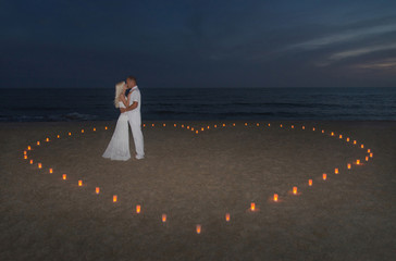 Young couple in candles heart at sea beach against sunset