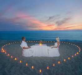 couple at beach romantic dinner with candles heart