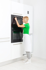 woman press button modern kitchen appliance